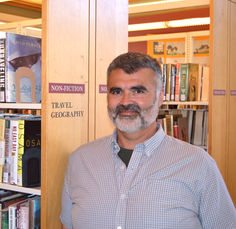 Matthew Graff, the incoming executive director at Skidompha Library in Damariscotta, stands among the bookshelves June 24. Graff officially took the reins Monday, July 1. (Evan Houk photo)