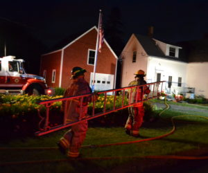 Bristol firefighters carry a ladder on the scene of a house fire at 2189 Bristol Road in Pemaquid the evening of Friday, July 19. (Maia Zewert photo)