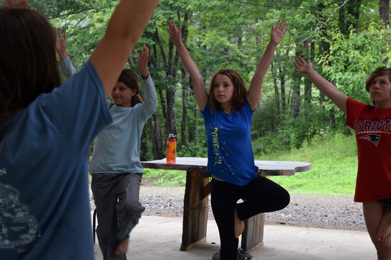 From left: Lina Remer, Gabriela Dotson, and Lydia Glidden demonstrate a yoga pose during the closing circle of a Hearty Roots camp at Hidden Valley Nature Center in Jefferson on Friday, July 12. (Jessica Clifford photo)