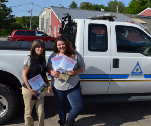 Melissa Temple, deputy director of the Lincoln County Emergency Management Agency, and Maia Zewert, marketing and engagement coordinator for Lincoln County Publishing Co., hold copies of the 2019 Lincoln County Road Atlas. (John Roberts photo)