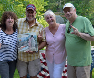Mill Pond Inn co-owners Sherry (far left) and Bobby (far right) Whear flash peace signs with guests Nick and Bobbi Ercoline as Nick holds the Woodstock concert album, which features a photo of the Ercolines embracing. The famous music festival was 50 years ago this August. (Evan Houk photo)