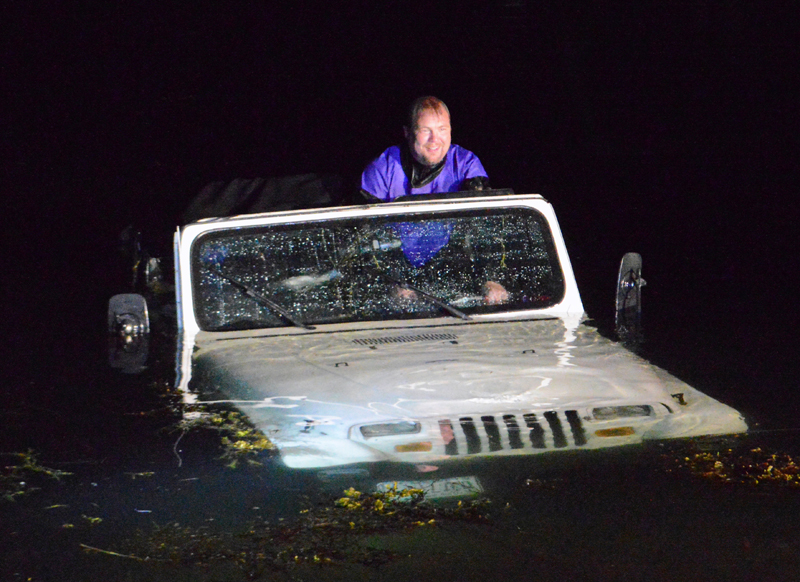 Local diver David Gallagher steers a Jeep Wrangler as a truck pulls it out of the water at Eugley Landing in South Bristol the night of Monday, July 29. Quick Turn Auto Repair and Towing Inc., of Damariscotta, pulled the Jeep out. (Evan Houk photo)