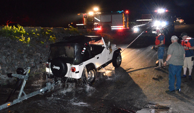 A 1987 Jeep Wrangler sheds water as Quick Turn Auto Repair and Towing Inc., of Damariscotta, pulls it back onto the boat ramp at Eugley Landing in South Bristol the night of Monday, July 29. (Evan Houk photo)