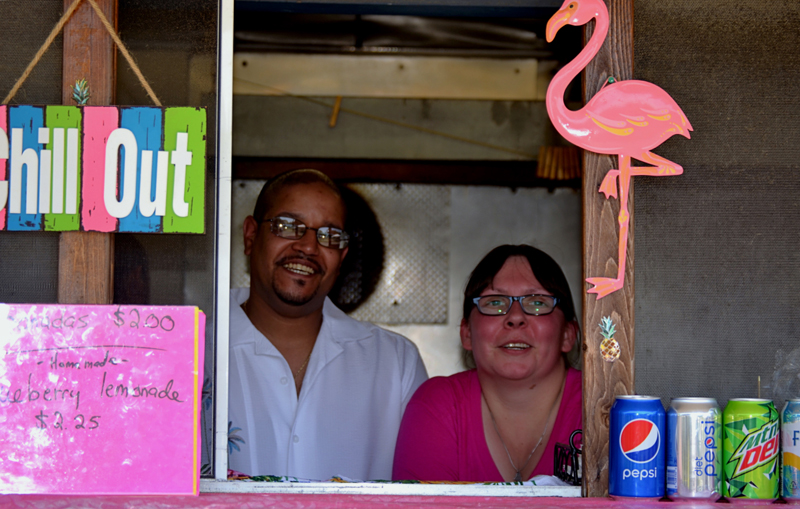 Alex Echevarria and Daisey Cunningham, of Wiscasset, stand behind the counter of their Puerto Rican food stand, Maritza's Place, at Montsweag Flea Market in Woolwich on July 3. (Nettie Hoagland photo)