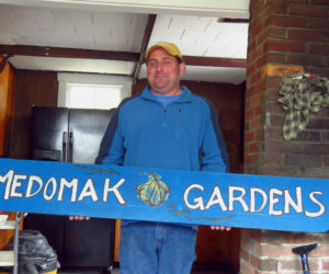 """Tony Gallace holds a """"Medomak Gardens"""" sign. Gallace manages the Feed the Need program, which is partnering with other local organizations to launch the Edible Waldoboro program."""