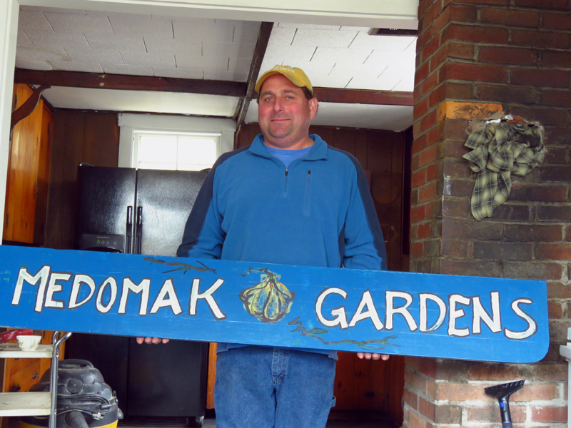 "Tony Gallace holds a ""Medomak Gardens"" sign. Gallace manages the Feed the Need program, which is partnering with other local organizations to launch the Edible Waldoboro program."