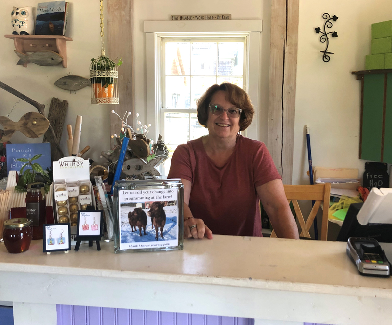 Board member and store volunteer Lori Bryant stands behind the counter of the Morris Farm Store.
