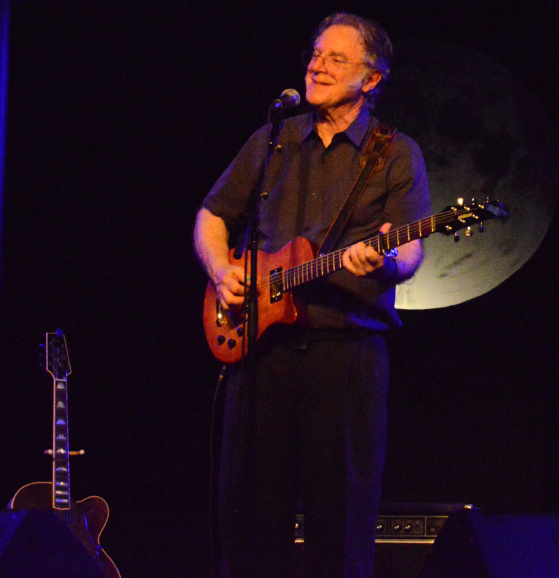 John Sebastian, with an enlarged image of the moon as his backdrop, delights the sold-out crowd out the Opera House at Boothbay Harbor with plenty of stories and song on Thursday, July 25. (Evan Houk photo)