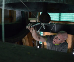 Rob Gregory adjusts the tension on the pulley system he devised that will allow the manual ringing of the bell at Damariscotta Baptist Church to continue, despite the installation of automatic controls. (Evan Houk photo)