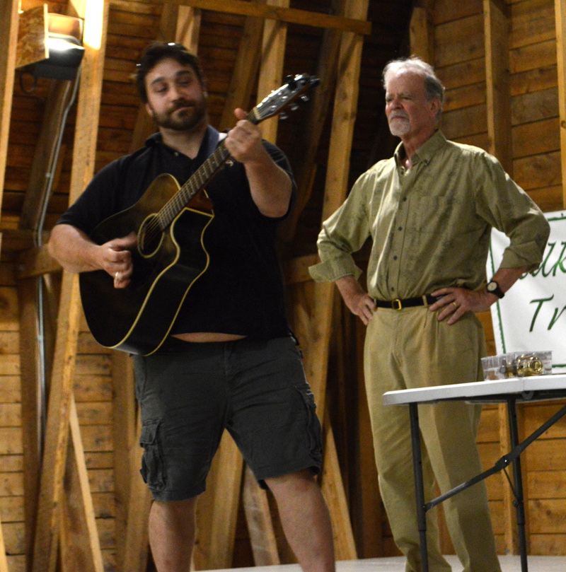 "Gianni Barbera strums a parody of Simon & Garfunkel's ""The Sound of Silence,"" singing about the ""rising mound of garbage"" as Michael Uhl looks on during the ""Talking Trash!"" forum at Darrows Barn in Damariscotta on Thursday, Aug. 22. (Evan Houk photo)"