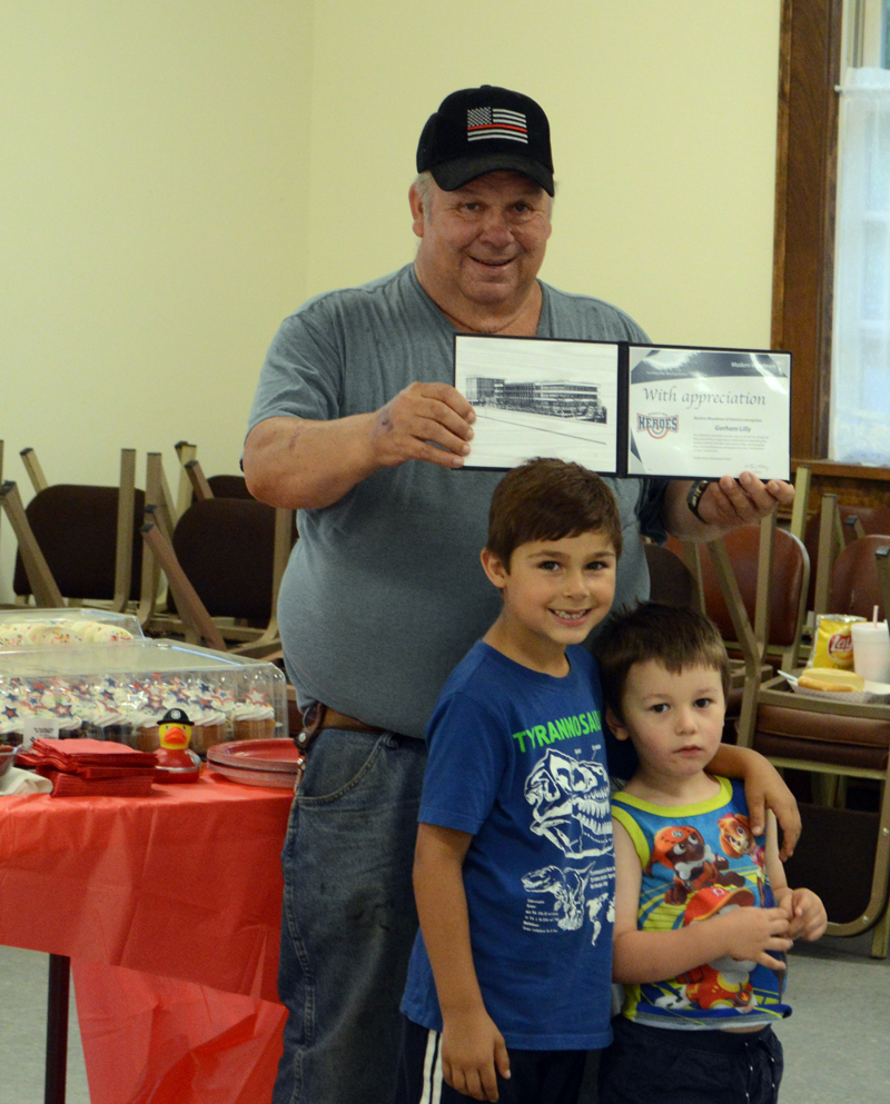 Capt. Gorham Lilly, of the Dresden Fire Department, displays his Hometown Hero award with his grandsons, Spencer Lilly (left) and Liam Aarons. The Modern Woodmen of America Hometown Heroes Program presented the award to Lilly for his 57 years of service to the department. (Evan Houk photo)