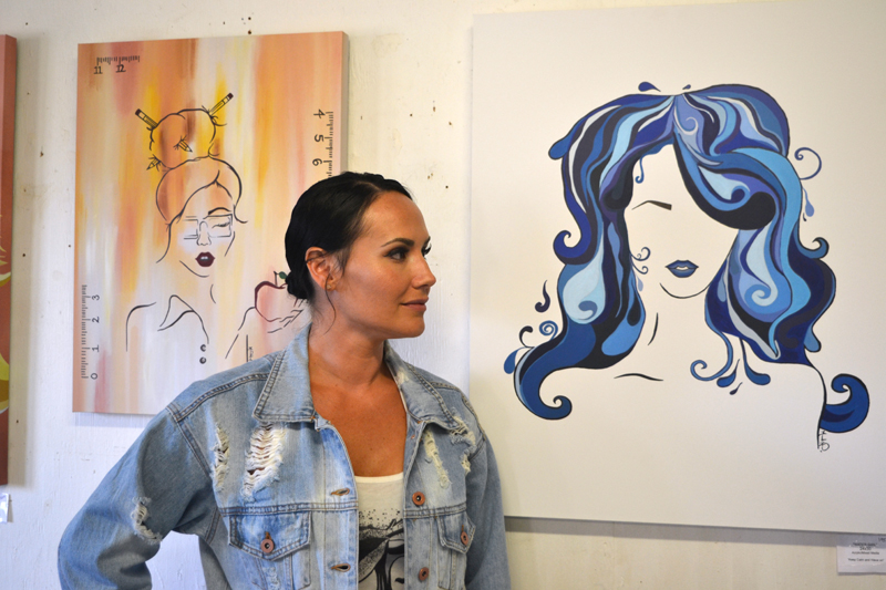 "Whitefield artist Manda Hard poses between her paintings ""Teacher Girl"" (left) and ""Water Girl"" at the opening reception for her art exhibit at Sheepscot General in Whitefield on Friday, Aug. 2. (Christine LaPado-Breglia photo)"