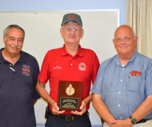 """Damariscotta Deputy Fire Chief James """"High Speed"""" Hall accepts the Chief Bob Maxcy Lifetime Achievement Award from the Lincoln County Fire Chiefs Association as President Roger Whitney (left) and Vice President Paul Leeman Jr. look on. (J.W. Oliver photo)"""