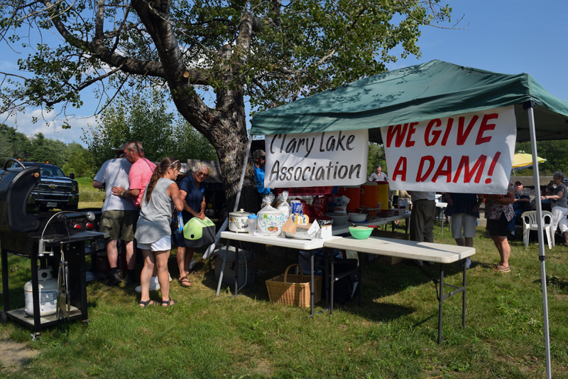 "Clary Lake Association members prepare for a cookout after the association's annual business meeting Sunday, Aug. 4. A sign bears the association's slogan, ""We give a dam!"" (Jessica Clifford photo)"