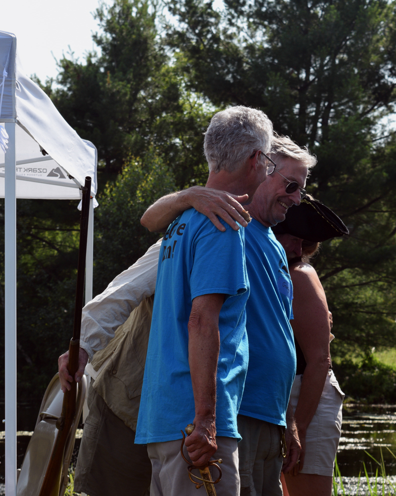 Clary Lake Association Secretary George Fergusson wraps his arm around former association President Malcolm Burson after giving him a dramatic thank you for his ongoing dedication to the association and knighting him as Sir George of Clary - Lake Keeper for Life. (Jessica Clifford photo)