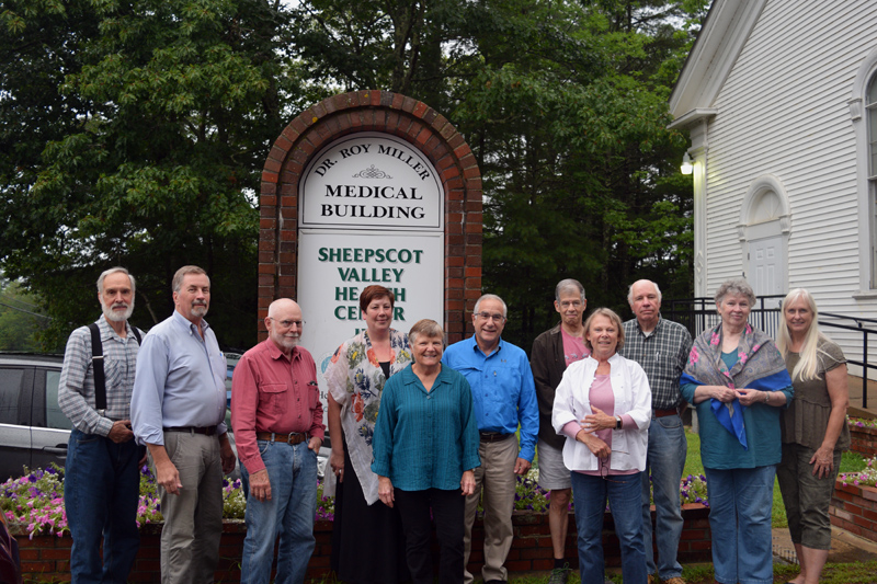 The Sheepscot Valley Health Center Board of Directors poses with Lisa and Dr. Roy Miller in front of the new sign for the Dr. Roy Miller Medical Building. (Jessica Clifford photo)