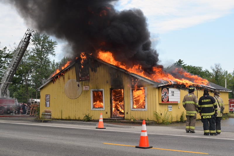 Local firefighters watch the circa-1960s Huber's Market building go up in flames during a training exercise in Wiscasset on Sunday, Aug. 4. The site will become part of the parking lot for a new Dollar General store. (Jessica Clifford photo)