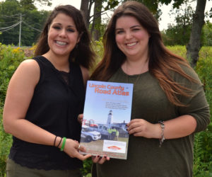 Amanda Reibel (left), the marketing and community relations specialist for Servpro of Bath/Brunswick, and Maia Zewert, the marketing and engagement coordinator for The Lincoln County News, hold a copy of the 2019 edition of the Lincoln County Road Atlas. (Amber Clark photo)