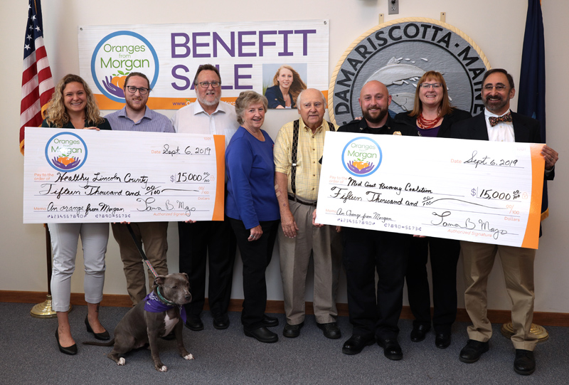 The family behind Oranges from Morgan presents $15,000 checks to Healthy Lincoln County and the Midcoast Recovery Coalition at the Damariscotta town office Friday, Sept. 6. From left: Jess Breithaupt, of Healthy Lincoln County; Derek Mayo, with Marley; Joe Mayo; Florence and Ernest Bourgon; Damariscotta Police Chief Jason Warlick; Tamra Mayo; and Dr. Ira G. Mandel, of the Midcoast Recovery Coalition. (Photo courtesy John Maciel)