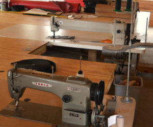 The industrial sewing machines at Benjamin Zook's Cooper Canvas shop in Whitefield. The machine at rear measures a yard across. (Christine LaPado-Breglia photo)