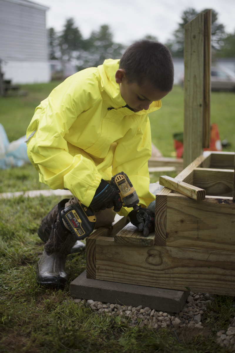 Jack Heller, 10, of Waldoboro, uses a drill as he works on a new set of stairs at East Ridge Mobile Home Park in Waldoboro on Community Cares Day, Saturday, Sept. 7. (Jessica Picard photo)