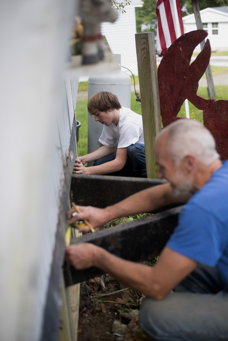 Shane Woods, back, a recent graduate of Medomak Valley High School, and Bill Hinkley, a teacher at the school, work to replace the skirt on Woods' home Sunday, Sept. 8. (Jessica Picard photo)
