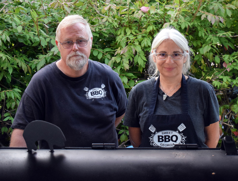 Ken Flower, owner of Sweet Georgia BBQ, stands with Susan Concolino behind his wood-fired smoker. The barbecue stand has moved from Bristol to a new location in the parking lot of Milling Around at 67 Main St. in Newcastle. (Evan Houk photo)
