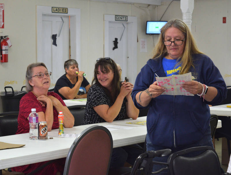 From left: Cindy Bailey and Charlotte Simmons wait with anticipation as Huntoon Hill Grange member Debbie Kovacs reviews Bailey's bingo card during the Smerdon family benefit at the Grange in Wiscasset on Sunday, Sept. 22. (Jessica Clifford photo)