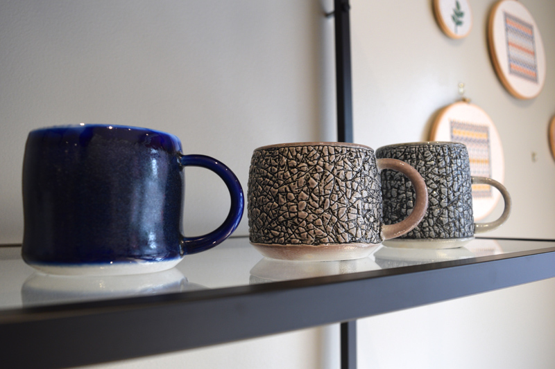 A few of Midcoast Craft co-owner Dennis Chouinard's mugs on display. (Jessica Clifford photo)