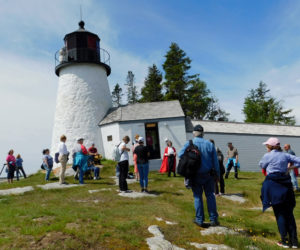 Participants visit the Burnt Island Lighthouse during a Maine Maritime Museum Lighthouse Legends and Lore Cruise with Red Cloak Tours.