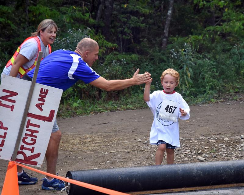 A volunteer high-fives a racer.