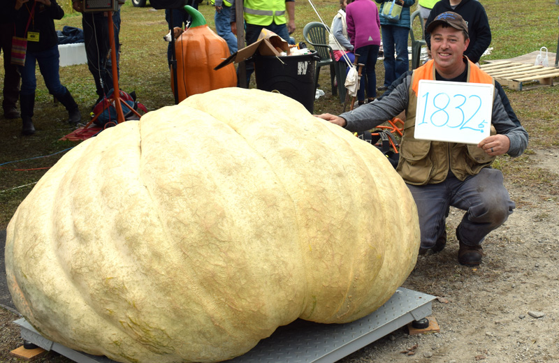 Edwin Pierpont, of Jefferson, kneels with his state record-breaking 1,832.5-pound pumpkin during the 13th annual Damariscotta Pumpkinfest giant pumpkin weigh-off at Pinkham's Plantation in Damariscotta on Sunday, Oct. 6. (Evan Houk photo)