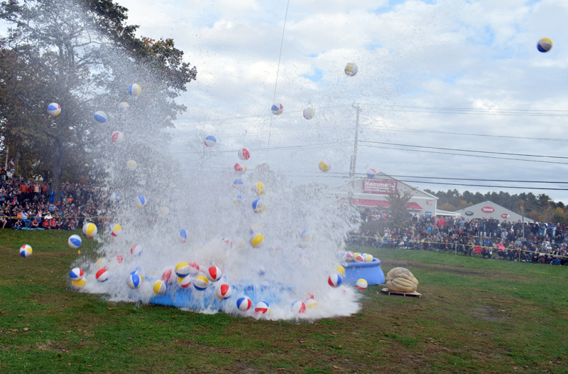 Beach balls and water fly as the first giant pumpkin touches down from its 180-foot journey into an inflatable swimming pool during the pumpkin drop at Round Top Farm in Damariscotta on Sunday, Oct. 13. (Evan Houk photo)