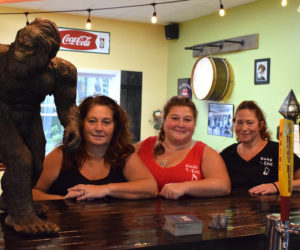 From left: Y-Knot Underground co-owners Carol Heaberlin, Mindy Jones, and Elayne Trotta sit at the bar next to the new Damariscotta eatery's mascot, Bigfoot. (Evan Houk photo)