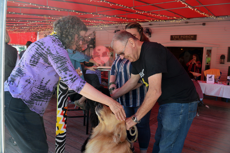 The Rev. Maria Hoecker, of St. Columba's Episcopal Church in Boothbay Harbor, blesses Decker, while Jim Singer holds the dog's leash during the Action for Animals Maine launch party at Brady's restaurant. (Jessica Clifford photo)