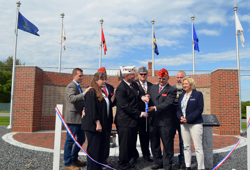 American Legion officials and dignitaries cut the ribbon for the new POW/MIA memorial at the Legion's state headquarters in Winslow on Saturday, Sept. 28. From left: U.S. Rep. Jared Golden, American Legion Auxiliary State President Virginia Chaput; past American Legion National Cmdr. Tony Jordan (obscured); American Legion State Cmdr. Matthew Jabaut; Sons of the American Legion State Cmdr. Ron Marr; American Legion National Cmdr. James Oxford; American Legion Riders State Cmdr. Mike Lallemand, and Michelle Michaud, representing U.S. Sen. Susan Collins. (Charlotte Boynton photo)