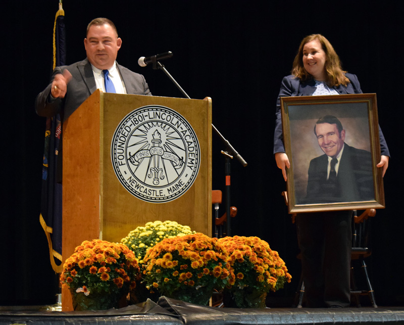 Lincoln Academy Board of Trustees President Judi Hilton holds up a portrait of the late LA Principal Arthur Dexter as LA graduate and Maine District Court Judge Eric J. Walker tells a story about Dexter during the installation ceremony for new Head of School Jeffrey Burroughs on Saturday, Oct. 5. (Evan Houk photo)