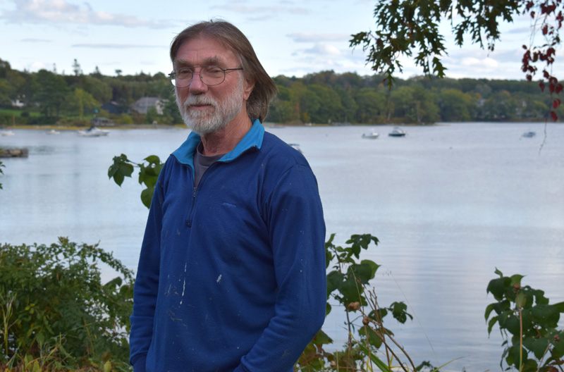 """Nigel Calder, author of the """"Boatowner's Mechanical and Electrical Manual,"""" stands behind his home on the Damariscotta River in Newcastle, Friday, Oct. 4. Now in its fourth edition, the book has sold over 300,000 copies worldwide. (Evan Houk photo)"""