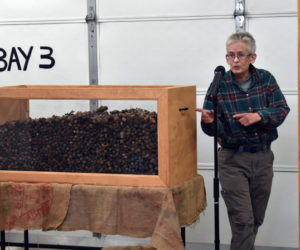 Mary Winchenbach, founder and owner of Tirdy Works, gestures toward a box of moose droppings during a television shoot at the Somerville fire station Thursday, Oct. 24. (Alexander Violo photo)