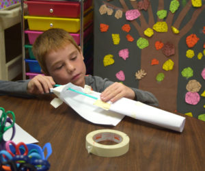 Max Hersom, a third grader at Whitefield Elementary School, attempts to build a rocket out of paper, a straw, and tape. (Jessica Clifford photo)