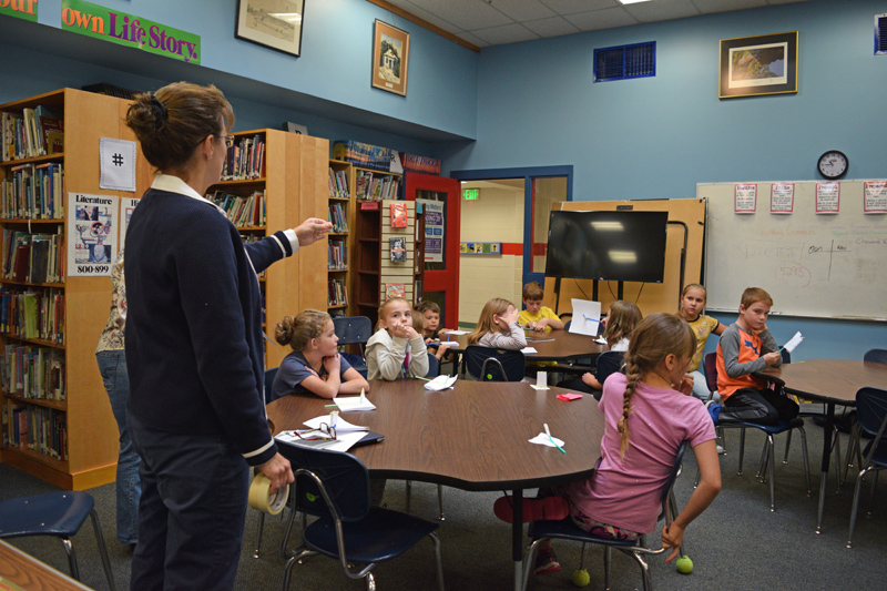 Clarissa Howard, learning commons guide at Whitefield Elementary School, asks students questions after they made rockets from paper, tape, and a straw on Friday, Oct. 4. (Jessica Clifford photo)