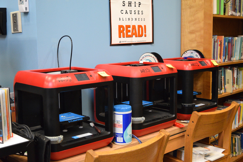A row of 3D printers in the learning commons at Whitefield Elementary School. Students are using the technology more this year. (Jessica Clifford photo)