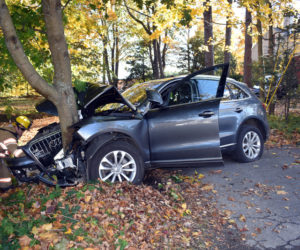 A firefighter inspects an Audi SUV after a crash near Wiscasset village the afternoon of Saturday, Oct. 26. (Alexander Violo photo)