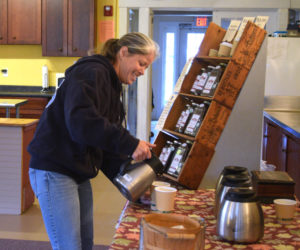 Crystal Lewis pours cream into her coffee at The Morris Farm, the location for the Wiscasset Winter Farmers Market. (Jessica Clifford photo)
