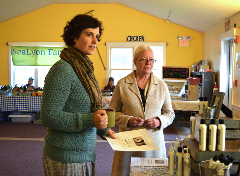 Anna Blank, farm education director for The Morris Farm, stands next to Penny Theall in front of the Blue Tin Farm stand at the Wiscasset Winter Farmers Market on Thursday, Oct. 17. (Jessica Clifford photo)
