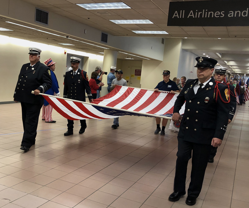 Maine firefighters carry the American flag during the Honor Flight Maine homecoming parade at the Portland International Jetport on Sept. 22. (Photo courtesy Kathleen Onorato)