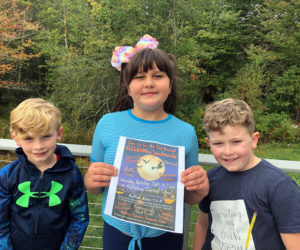 From left: Noah Irons, JoJo Shea, and Brayden Irons with a 2019 NobleBOOro Spooktacular poster.