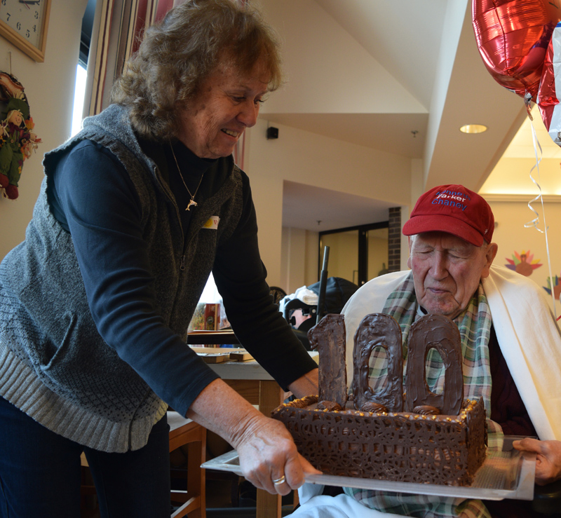 Nancy Hanna brings a 100th birthday cake to her father, Kenneth Chaney, during a celebration at the Maine Veterans' Home in Augusta on Friday, Nov. 15. (Jessica Clifford photo)