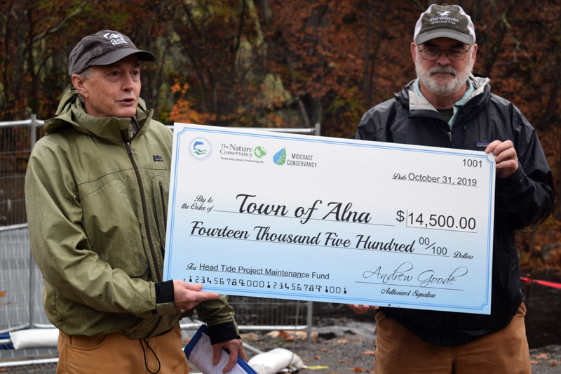 From left: Andrew Goode, vice president of U.S. programs at the Atlantic Salmon Federation, presents a check for $14,500 to Alna Third Selectman Greg Shute for maitenance of the Head Tide Dam site. (Jessica Clifford photo)