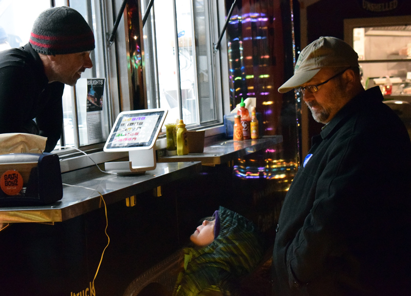 A young patron struggles to see over the counter to place an order with Warren Busteed, owner of the Salty Boyz food truck, at Food Trucks A-Go, the new food truck court on Route 27 in Boothbay, Saturday, Nov. 23. (Evan Houk photo)